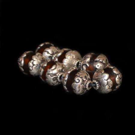 Sieben in Silber gefasste Resinperlen